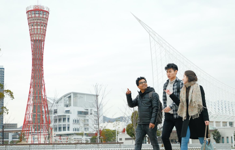 Three international students walking together near Kobe Port.